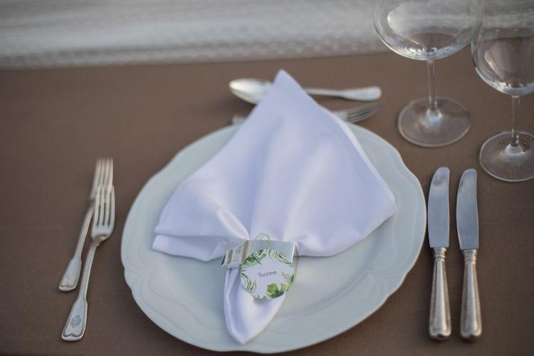 Gedeckter Tisch mit brauner Tischdecke, Spitzentischdecke und Platzkarte im Greenerystyle