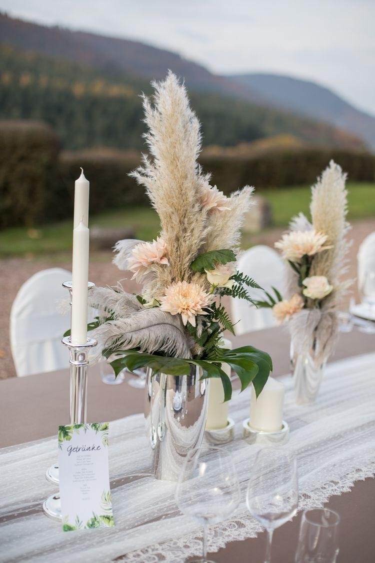 Silberne Vase mit apricot farbenen Blumen, Federn und Blattgrün