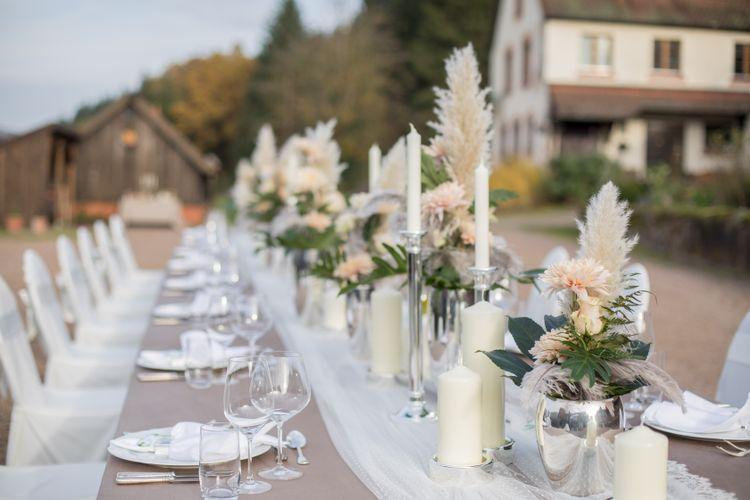 Silberne Vase mit apricot farbenen Blumen, Federn und Blattgrün, Spitzentischdecke, personalisierter Wein, silberne Kerzenstände