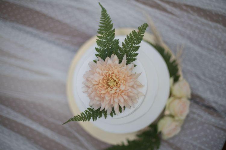 Hochzeitstorte mit Blattgrün und Apricotfarbenen Blumen dekoriert